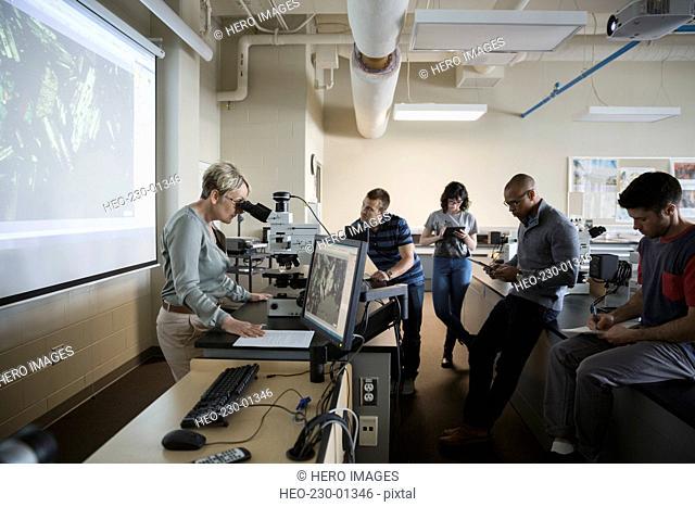 Science professor at microscope leading lesson in classroom