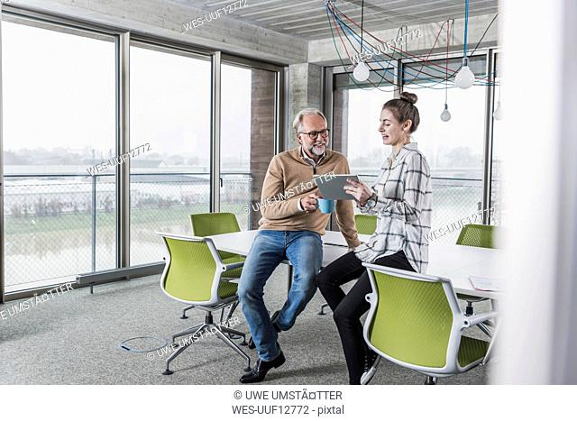 Casual mature businessman and young woman with tablet in conference room in office