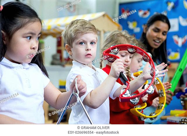 Nursery children playing with musical instruments in the classroom. One little boy is looking at the camera with a tambourine