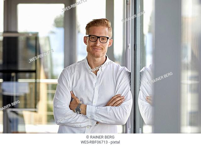 Portrait of smiling businessman in office leaning against window