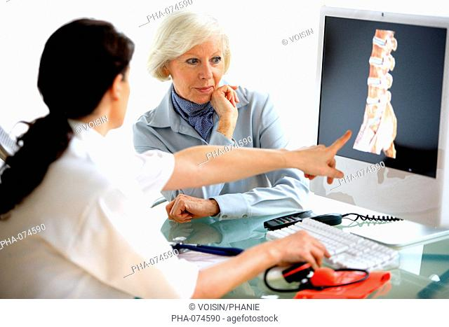 Doctor discussing backbone 3D CT scan with a patient