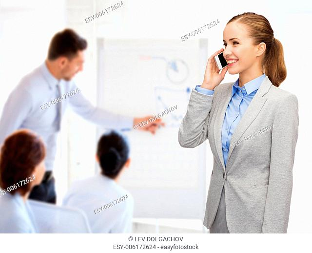 business, technology and education concept - friendly young smiling businesswoman with smartphone