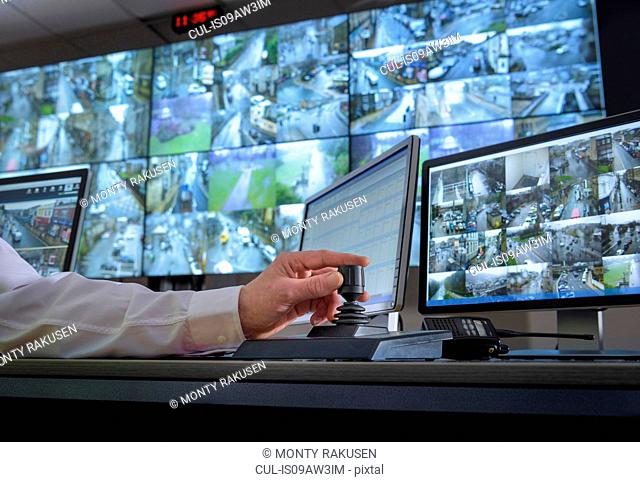 Detail of hand on camera control joystick in control room with video wall