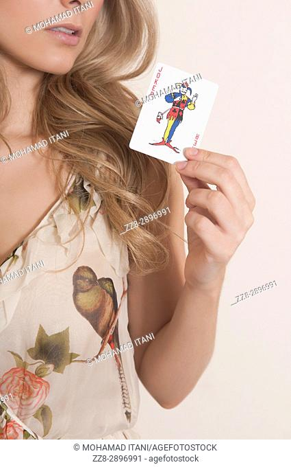 Woman holding a jocker playing card