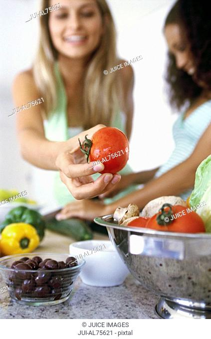 View of two women preparing a salad
