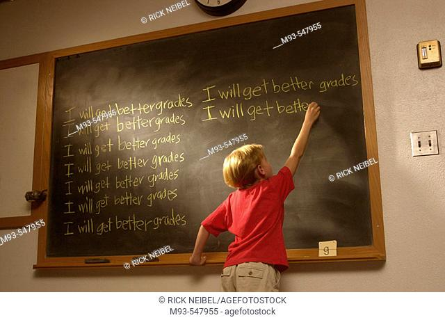 Young blond boy; red t-shirt; at wood-framed classroom blackboard writing 'I will get better grades'multiple times. Light highlighting blackboard and boy's...