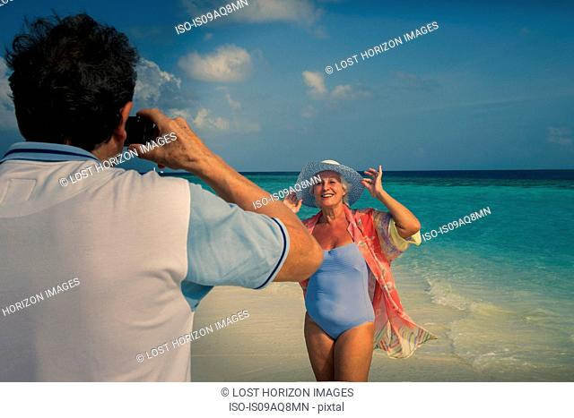 Man photographing senior woman, Maldives