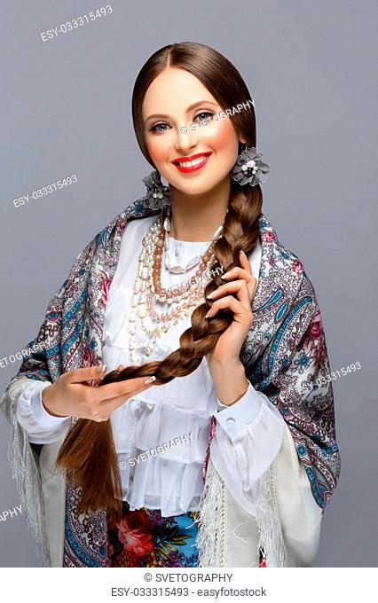 Happy beautiful young russian woman with very long braid in traditional shawl. Red lips. Over grey background