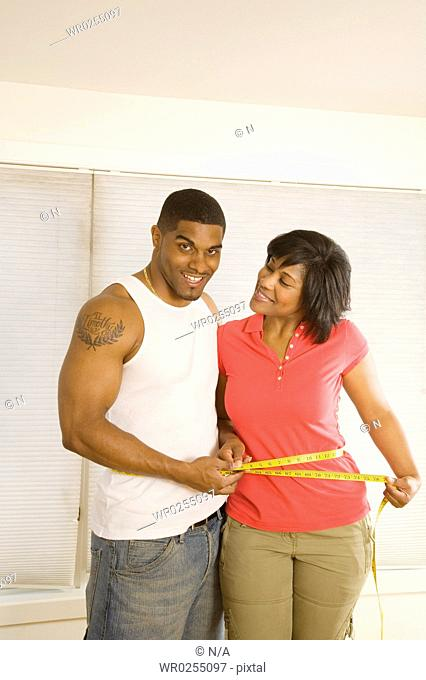 Man measuring wifes waist