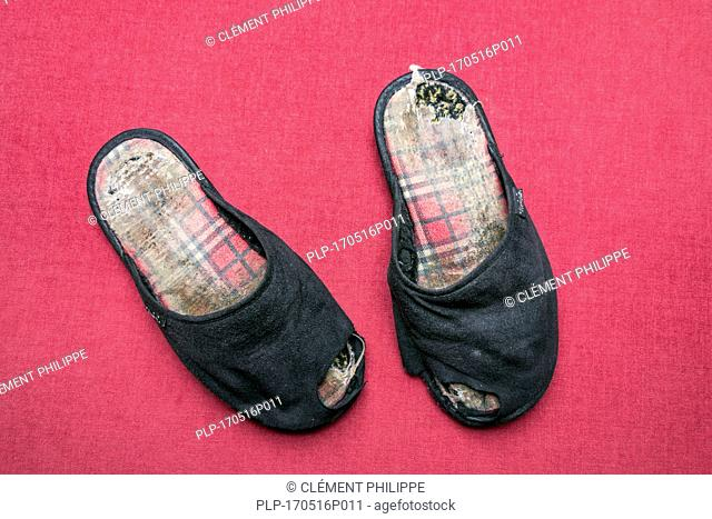 Couple of old worn black slippers with holes in them against red background