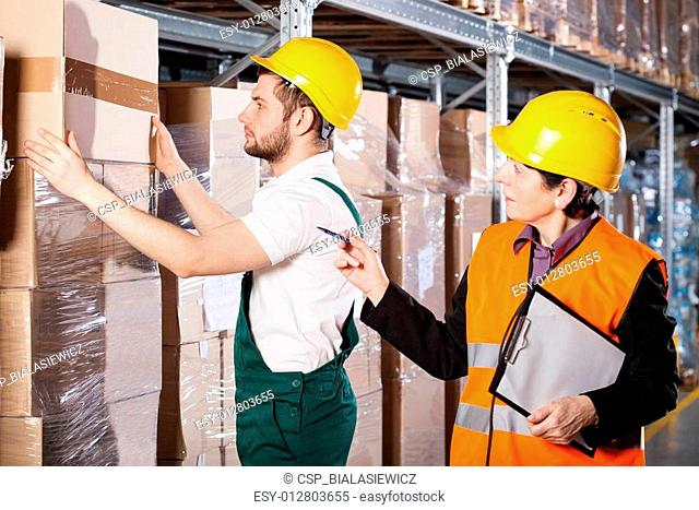 Manager with worker in warehouse