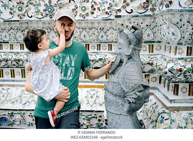 Thailand, Bangkok, Wat Arun, Father and mischievous daughter visiting the Buddhist temple