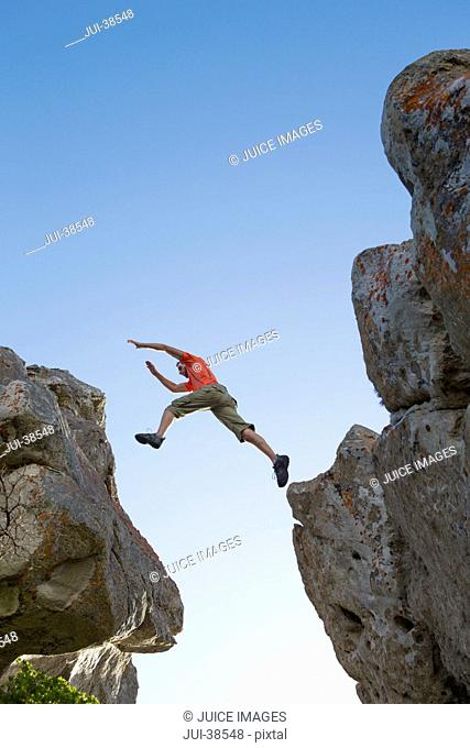 Male rock climber leaping between rocks