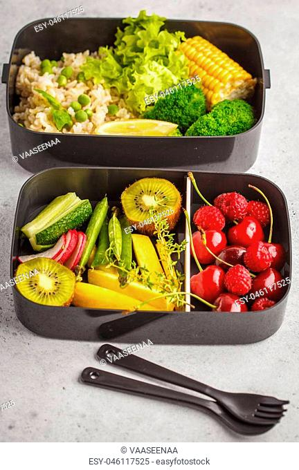 Healthy meal prep containers with brown rice, broccoli, vegetables, fruits and berries, vertical