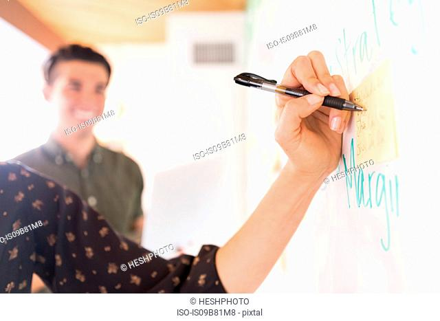Hand of businesswoman writing on whiteboard adhesive notes