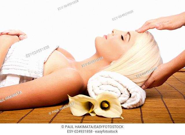 Beautiful young woman relaxing at spa getting therapeutic pampering forehead massage