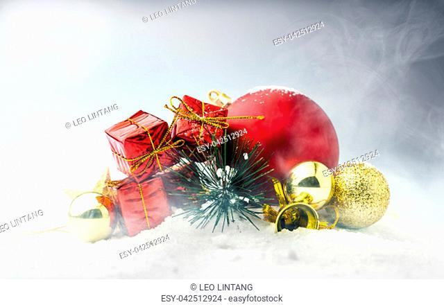 Red gift boxes with colorful christmas balls on the snow