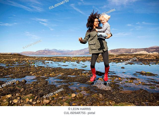Mother holding son jumping in Loch Eishort, Isle of Skye, Hebrides, Scotland