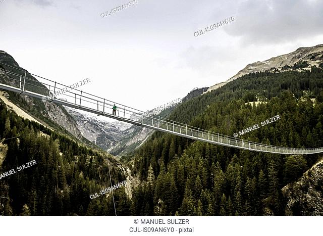 Low angle view of young female hiker crossing footbridge, Holzgau, Tirol, Austria
