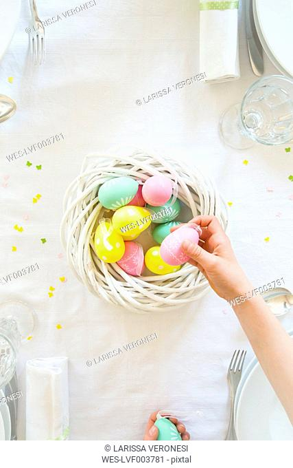 Little girl decorating dining table with Easter eggs