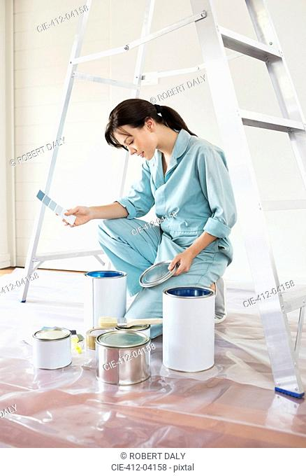 Woman examining paint cans