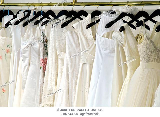 Bridal gowns hanging from a brass rack, in a retail store display