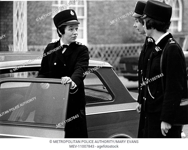 Three women police officers standing by a car, London. They are wearing the new style Norman Hartnell uniform, introduced in 1968