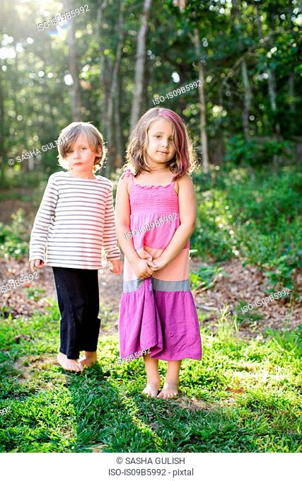 Portrait of boy and girl standing in garden