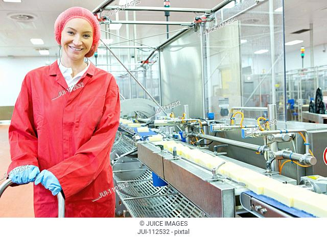 Portrait confident worker at production line in cheese processing plant