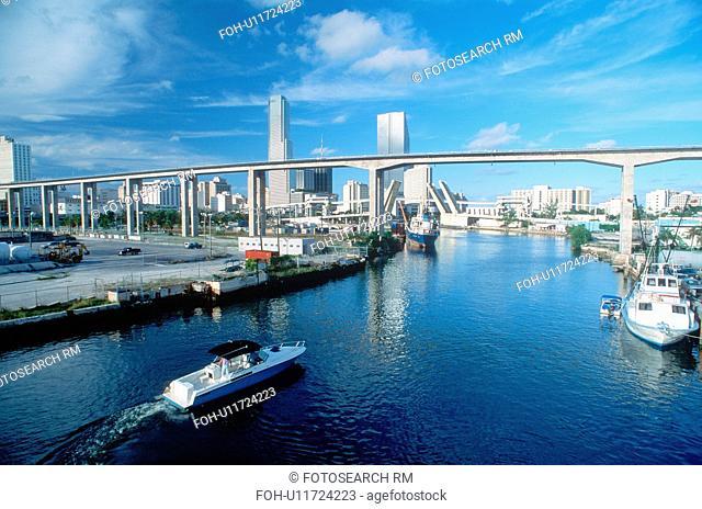 Waterway underneath metro rail line with skyline in background in Miami, Florida