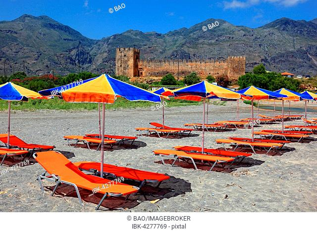 Colourful beach chairs and umbrellas in front of Frangokastello castle, Crete, Greece