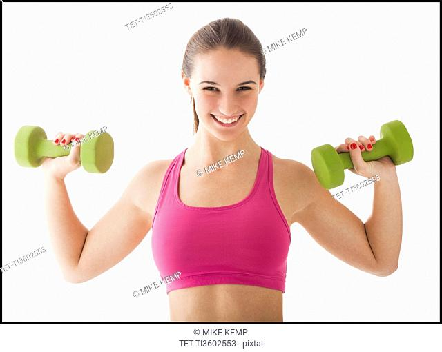 Studio portrait of young woman exercising with hand weights