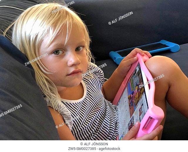 Blond girl, 3½ years old, holding a tablet computor and look at camera, in Ystad, Scania, Sweden
