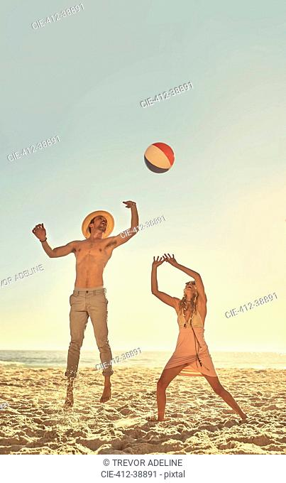 Young couple playing with beach ball on sunny summer beach