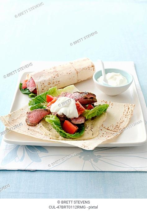 Plate of meat, salad and flatbread wrap