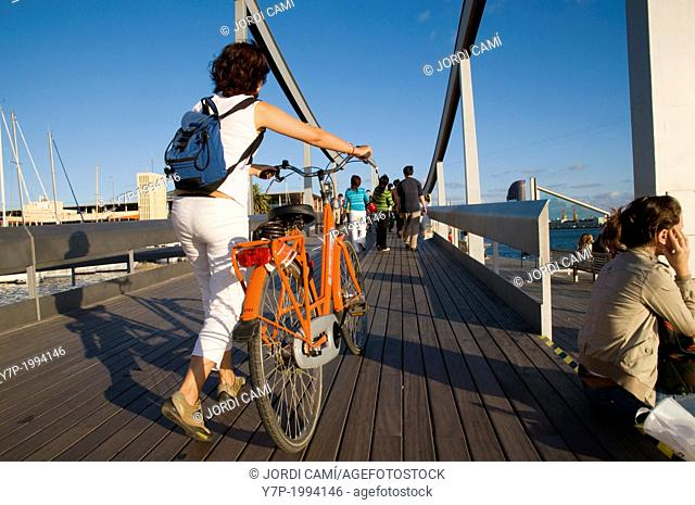 Young woman with a bicycle at Rambla del Mar footbridge to Maremagnum area ,Barcelona harbour, Catalonia, Spain