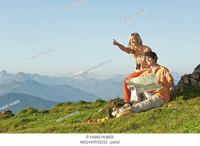 Young couple sitting on mountaintop, man holding map, smiling