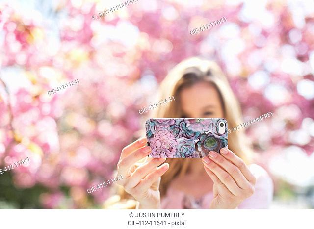 Woman taking self-portrait with cell phone outdoors