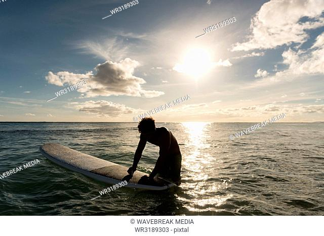 Male surfer surfing with surfboard in the sea