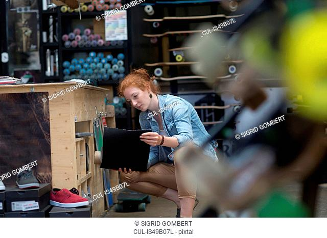 Woman working in skateboard shop, crouching, inspecting roll of skateboard grip tape
