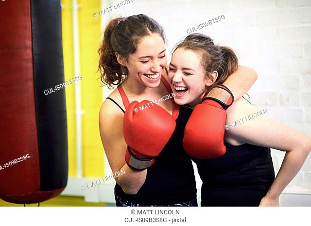 Two female boxing friends pretending to punch in gym