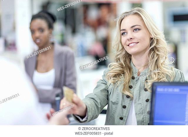 Woman at till paying with credit card