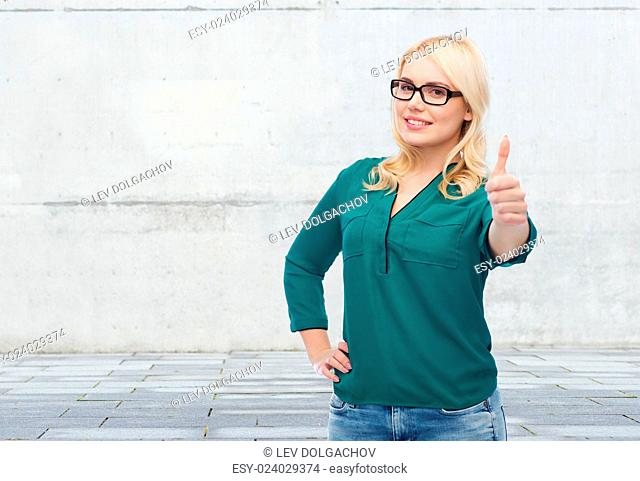 vision, optics, education, gesture and people concept - smiling young woman with eyeglasses showing thumbs up over gray concrete wall background