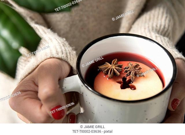 Woman's hands holding mug of apple cider
