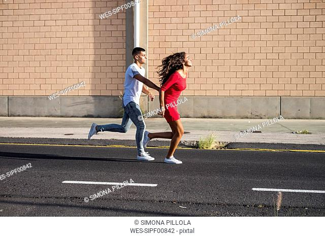 Teenage couple running hand in hand on a street