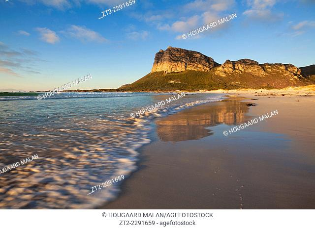 Landscape photo of a wave washing across a beach below hangklip mountain. Hangklip, Western Cape, South Africa