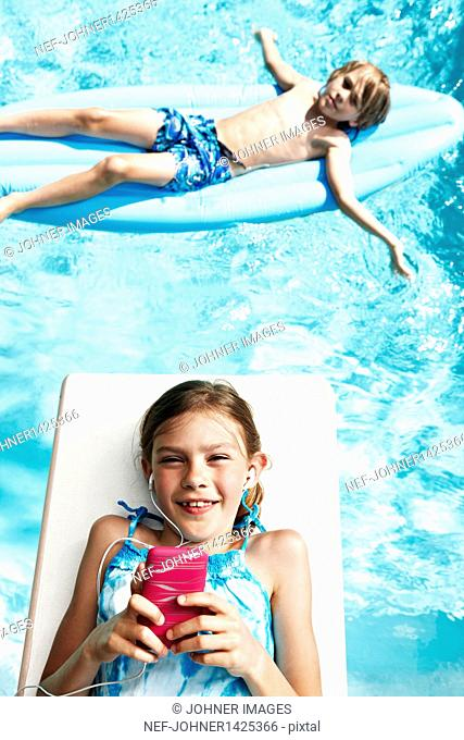 Boy and girl with mp3 player on pool rafts