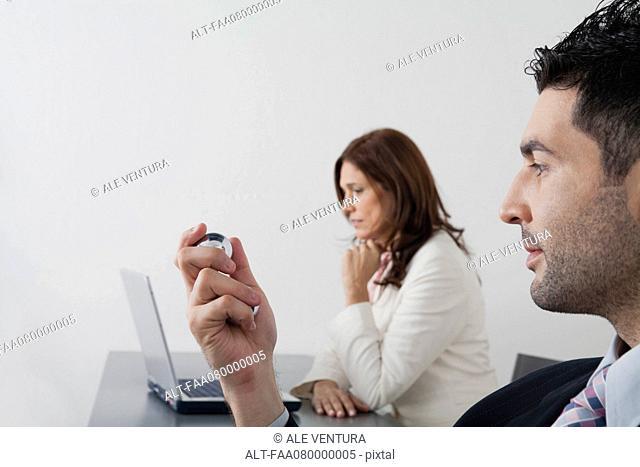 Businessman holding yin yang balls in office
