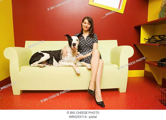 Young woman on couch with Great Dane