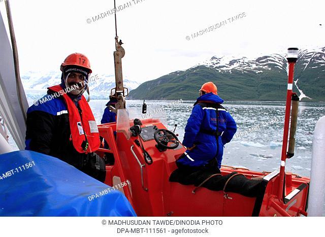 A man preparing for lowering lifeboat near Hubbard glacier ; the longest tidewater glacier in Alaska; Saint Elias  national park ; disenchantment bay ; Alaska ;...